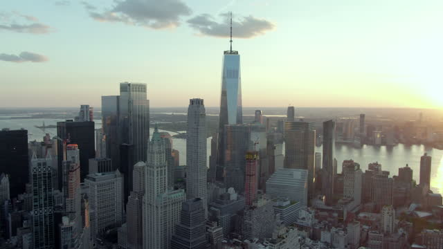 aerial shot of skyscrapers in financial district against sky, drone flying forward towards famous one world trade center in city during sunset - new york city, new york - aerial stock videos & royalty-free footage