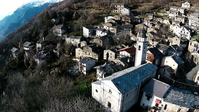 Aerial shot of small towns and mountains in Piedmont, Italy
