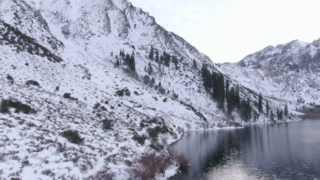 aerial shot of snowcapped mountains by convict lake against sky, drone ascending over white landscape during winter - mammoth lakes, california - mammoth lakes video stock e b–roll