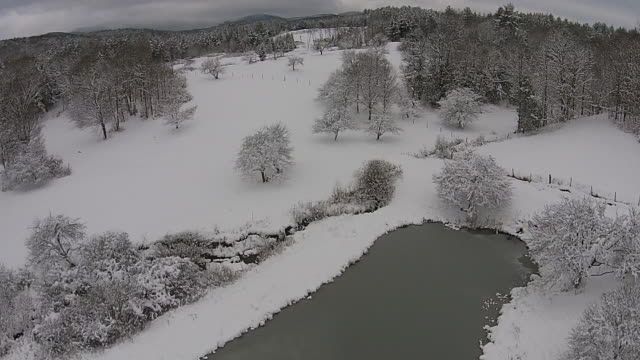 aerial shot of snowy countryside and lake - vermont stock videos & royalty-free footage