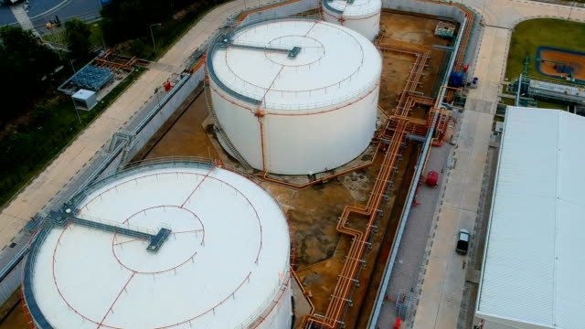 aerial shot of storage tanks at oil refinery or powerplant - petrol tank stock videos and b-roll footage