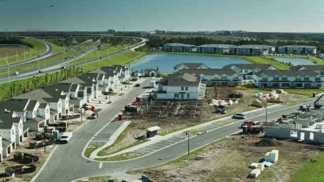 aerial shot of suburban development under construction near freeway - detached stock videos & royalty-free footage