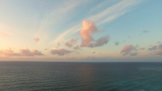 Aerial shot of sunrise over ocean in tropics