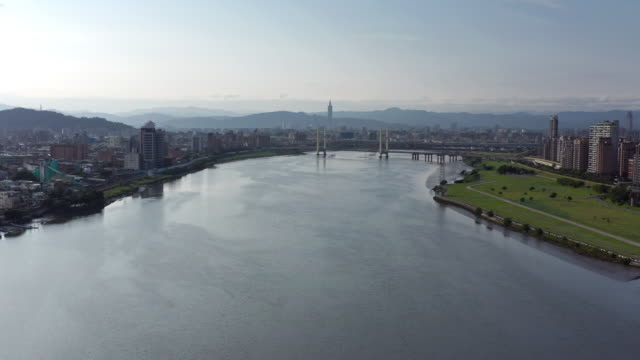 aerial shot of taipei, taiwan and the chongyang bridge over the tamsui river - 淡水点の映像素材/bロール