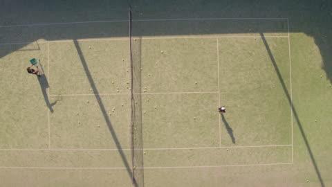 vídeos y material grabado en eventos de stock de toma aérea de adolescente practicando tenis - campo lugar deportivo