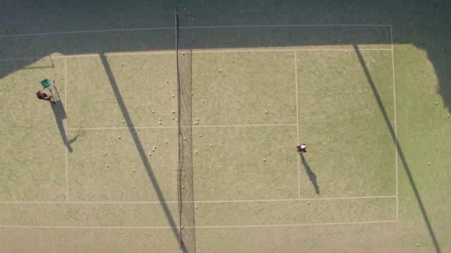 vidéos et rushes de aerial shot d'adolescent pratiquant le tennis - herbe