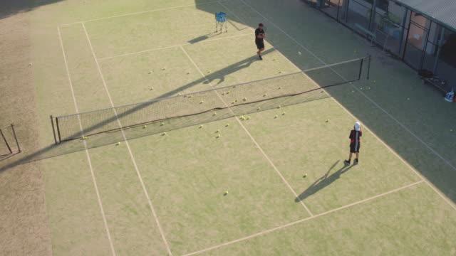 テニスの練習のティーンエイ ジャーの空中ショット - スポーツコート点の映像素材/bロール