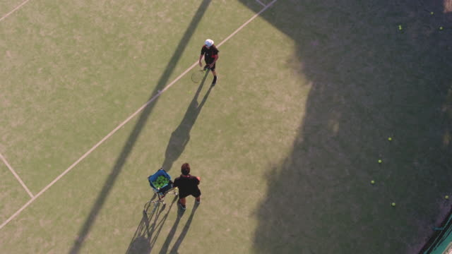 Aerial shot of teenager practicing tennis