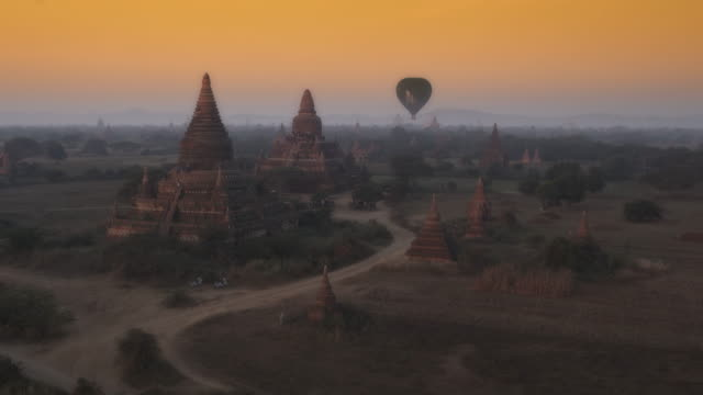 aerial shot of temples and hot air balloons at sunrise in myanmar - pagan stock-videos und b-roll-filmmaterial