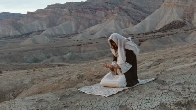 aerial shot of the camera circling jesus christ kneeling and praying with palms up on a desert hillside with a tent and mountains behind him at sunrise/sunset - praying stock videos & royalty-free footage