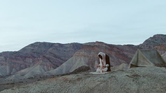 Aerial Shot of the Camera Circling Jesus Christ Kneeling and Praying with Palms Up on a Desert Hillside with a Tent and Mountains Behind Him at Sunrise/Sunset
