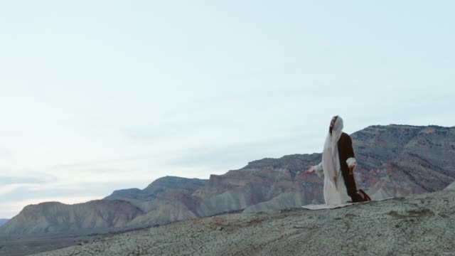 Aerial Shot of the Camera Circling Jesus Christ Kneeling and Praying with Arms Out on a Desert Hillside with a Tent and Mountains Behind Him at Sunrise/Sunset