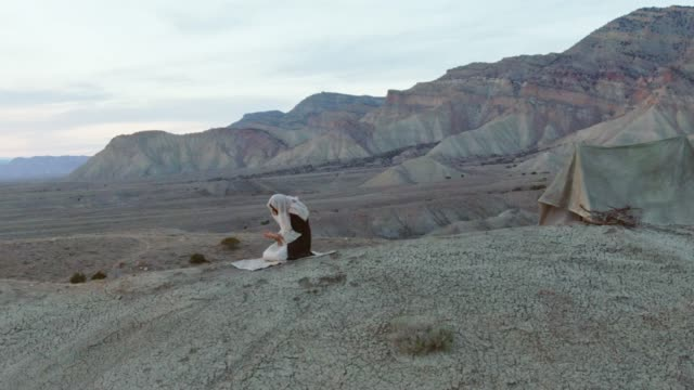 Aerial Shot of the Camera Pushing In as Jesus Christ Kneels and Prays with Palms Up on a Desert Hillside with a Tent and Mountains Behind Him at Sunrise/Sunset