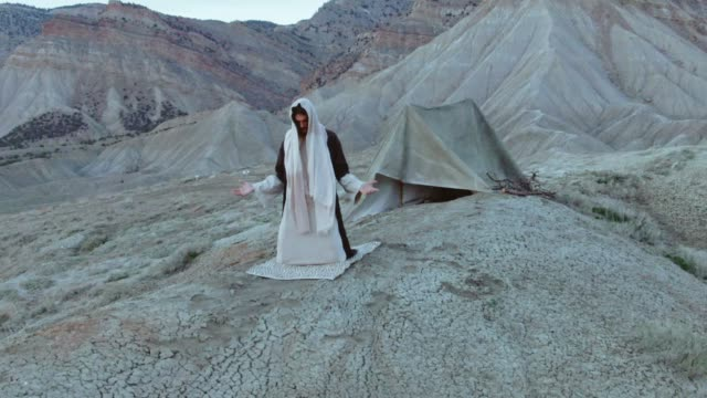 aerial shot of the camera pushing out as jesus christ kneels and prays with arms out on a desert hillside with a tent and mountains behind him at sunrise/sunset - temptation stock videos & royalty-free footage