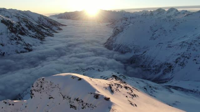 Tir aérien des montagnes du Caucase avec une mer de nuages au lever du soleil