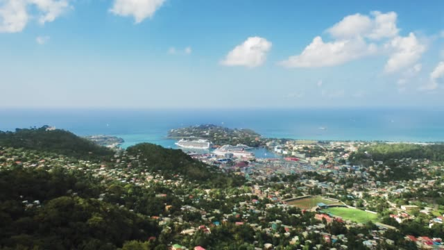 aerial shot of the city on the mountainous coast of the sea with a sports stadium and large ships in the bay (rodney bay, saint lucia) - st. lucia stock videos & royalty-free footage