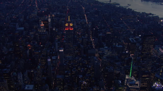 aerial shot of the empire state building at night. the camera approaches, tilts, and looks straight down at the skyscraper's spire and glowing lights. - spire stock videos & royalty-free footage