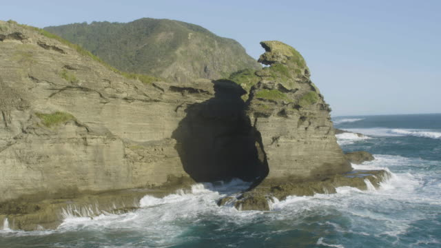 aerial shot of the eroded nun rock near the taitomo island - coastline stock videos & royalty-free footage