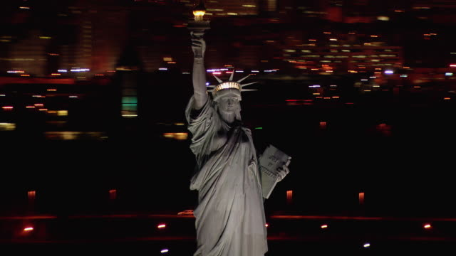 aerial shot of the famous statue of liberty at night with the lights of jersey city in the background. - statue of liberty new york city bildbanksvideor och videomaterial från bakom kulisserna