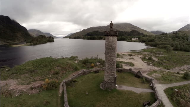 vidéos et rushes de aerial shot of the glenfinnan monument in the scottish highlands - scottish culture