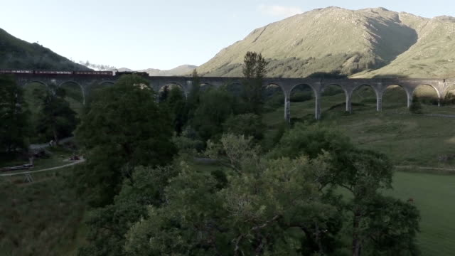 Aerial shot of the Jacobite Steam Train going over the Glenfinnan viaduct en route to Fort William in Scotland