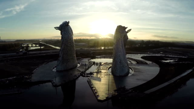 vídeos y material grabado en eventos de stock de aerial shot of the kelpies horse heads at the helix park in falkirk during sunrise - representación de animal