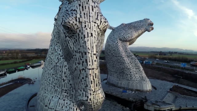aerial shot of the kelpies horse heads at the helix park in falkirk during sunrise - sculpture stock videos & royalty-free footage