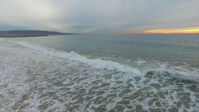 vídeos de stock, filmes e b-roll de aerial shot of the ocean and waves breaking on the beach. - goodsportvideo