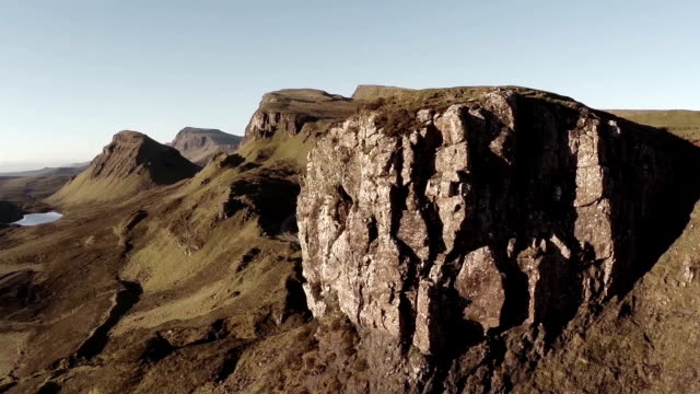 aerial shot of the quairang in skye (scotland) with morning light revealing dramatic landscape - スコットランド点の映像素材/bロール