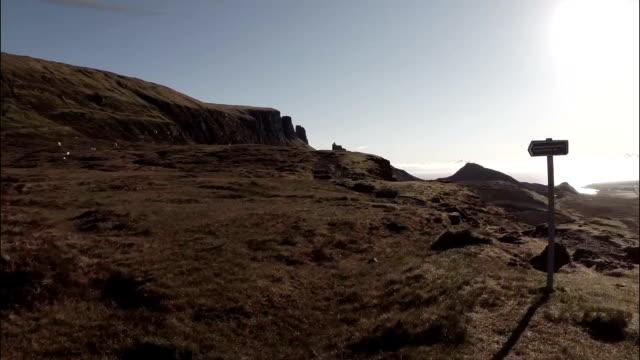 vidéos et rushes de aerial shot of the quairang in skye (scotland) with morning light revealing dramatic landscape - indication de direction