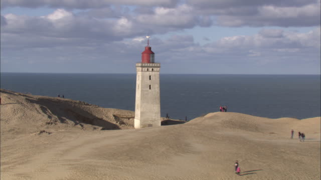 Aerial shot of the Rubjerg Knude lighthouse surrounded by shifting sand dunes.