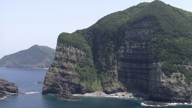 aerial shot of the rugged kashima cliffs on shimokoshiki island, which are more than 150 m in height. the different strata protruding from the cliffs... - ロックストラータ点の映像素材/bロール