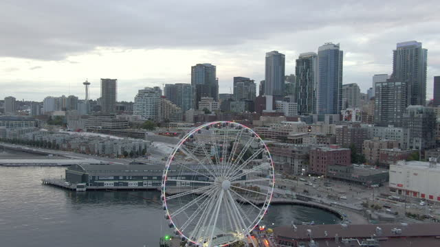 aerial shot of the seattle great wheel against buildings, drone ascending forward over piers on elliot bay in city against sky at dusk - スペースニードル点の映像素材/bロール