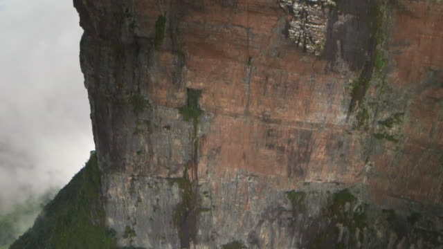 Aerial POV shot of the sheer cliff-face of a mountain in the Tepuis, Venezuela.
