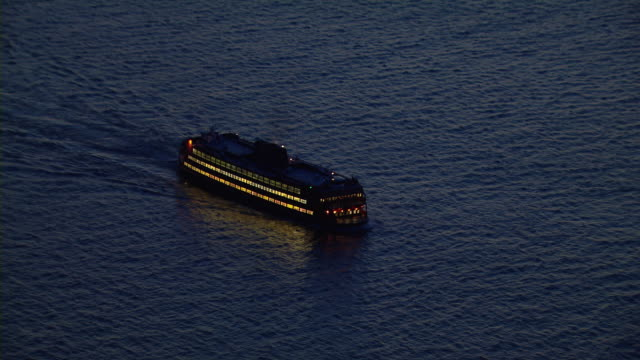 aerial shot of the staten island ferry as it crosses the waters of the new york harbor at night. - フェリー船点の映像素材/bロール