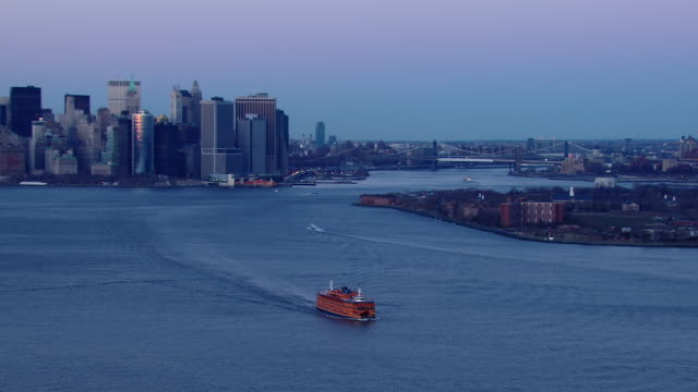 aerial shot of the staten island ferry sailing across the waters of the new york harbor at dusk. - new york harbor stock videos & royalty-free footage