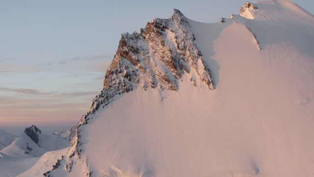 aerial shot of the steep side of a snow capped mountain in the swiss alps just after sunrise. - snowcapped mountain stock videos & royalty-free footage