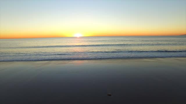 vídeos de stock, filmes e b-roll de aerial shot of the sun setting over a beach and ocean horizon. - goodsportvideo