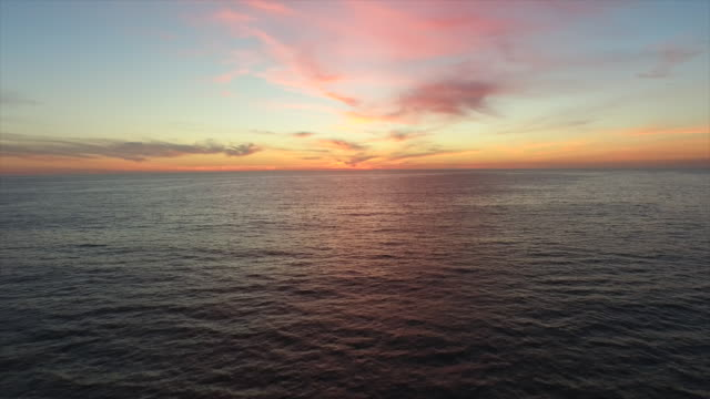 aerial shot of the sun setting over the ocean horizon. - pacific ocean stock videos & royalty-free footage