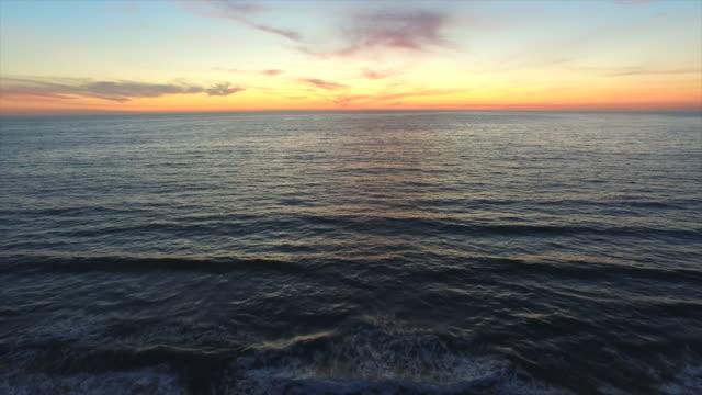 vídeos de stock, filmes e b-roll de aerial shot of the sun setting over the ocean horizon. - goodsportvideo