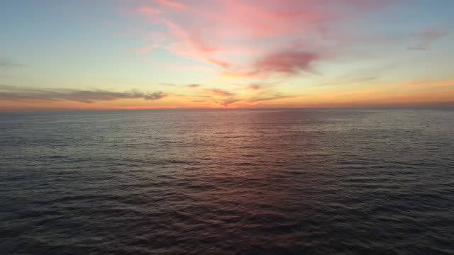aerial shot of the sun setting over the ocean horizon. - horizon stock-videos und b-roll-filmmaterial