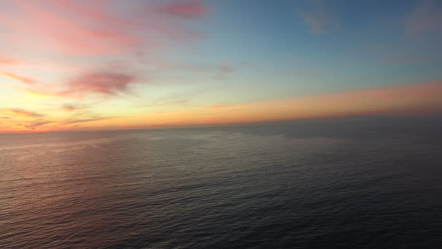 Aerial shot of the sun setting over the ocean horizon.