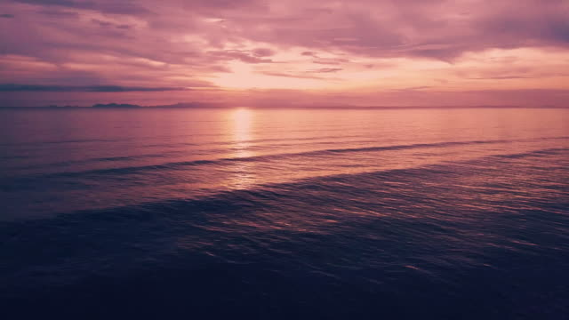 aerial shot of the sun setting over the ocean horizon. - purple stock videos & royalty-free footage