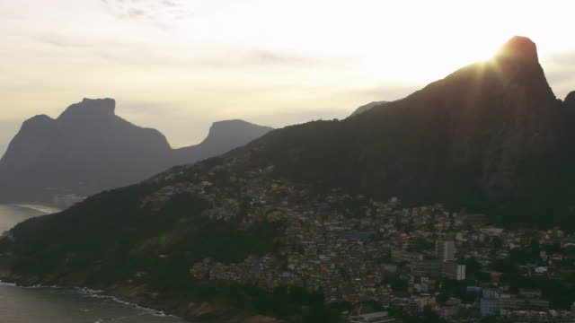 aerial shot of the vidigal favela and the do irmaos mountains - favela stock videos and b-roll footage