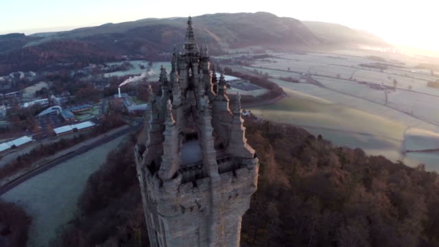 aerial shot of the wallace monument in scotland early on a summers morning with good light flare - stirling stock videos and b-roll footage