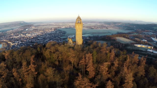 aerial shot of the wallace monument in scotland early on a summers morning with good light flare - スコットランド スターリング点の映像素材/bロール