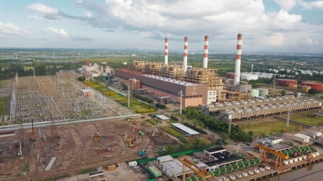 aerial shot of thermal power plant and stack and switch yard and construction site near the river in south east asia - turbine stock videos & royalty-free footage