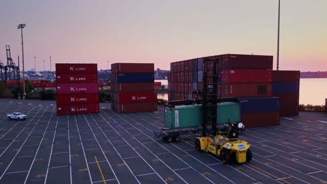aerial shot of top handler loading container truck - lastzug stock-videos und b-roll-filmmaterial