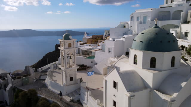 aerial shot of tourists at anastasi orthodox church in city, drone flying forward over whitewashed structures by sea on sunny day - santorini, greece - cyclades islands stock videos & royalty-free footage