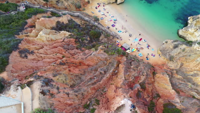 aerial shot of tourists at beach amidst rock formation, drone ascending over people near cliffs by sea - lagos, portugal - algarve stock videos & royalty-free footage